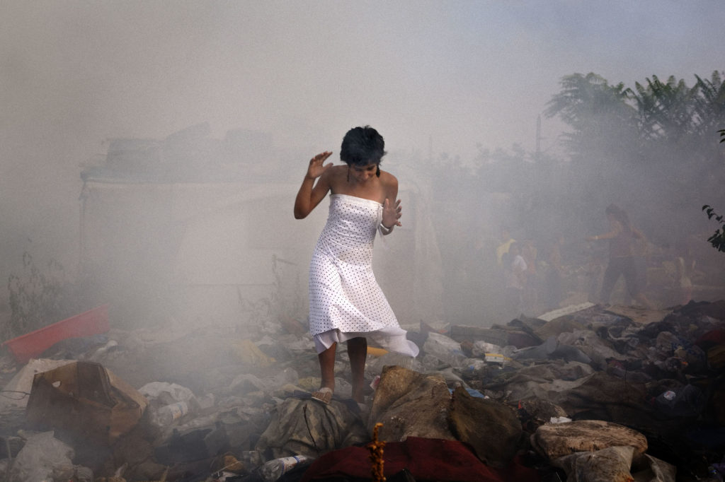 A young woman walks through a garbage-strewn field in the Nova Gazela settlement as a house burns down. The camp was razed the following day by Belgrade city authorities. August 2009.